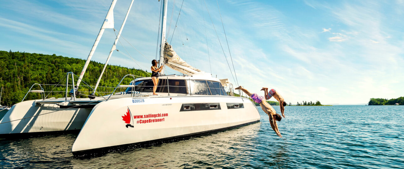 Swimmers dive from the deck of the Cape Bretoner 1 catamaran into bue waters of the Beas D'Or Lake
