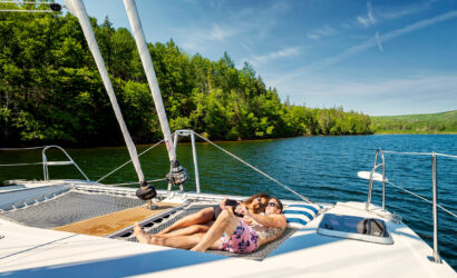 Sunbathers on the fore-deck of the Cape Bretoner 1 catamaran anchored near shore of the Bras D'Or Lake