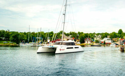 The Cape Bretoner 1 catamaran sailing out of Baddeck Harbour with village of Baddeck in the background